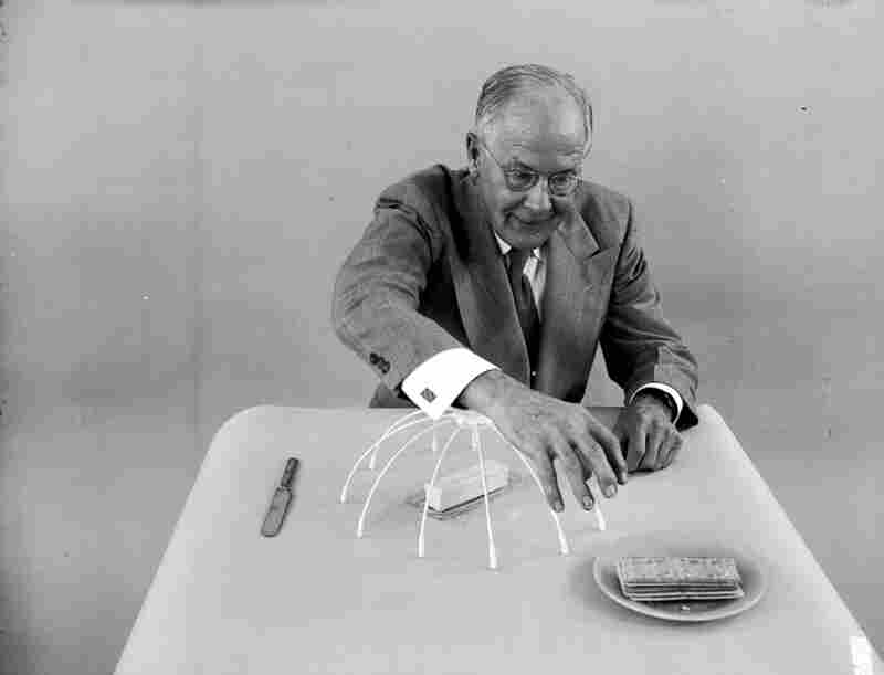 """Oakes demonstrates his """"sleeve protector"""" which covers a slab of butter to prevent him accidentaly touching it as he leans across a table."""