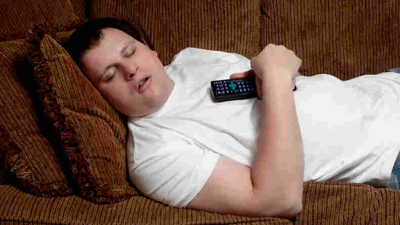 man lying asleep on his couch