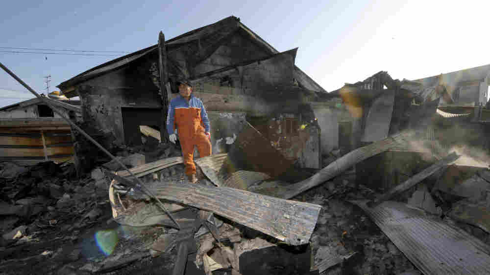A South Korean resident stands on the rubble of a destroyed house on Yeonpyeong