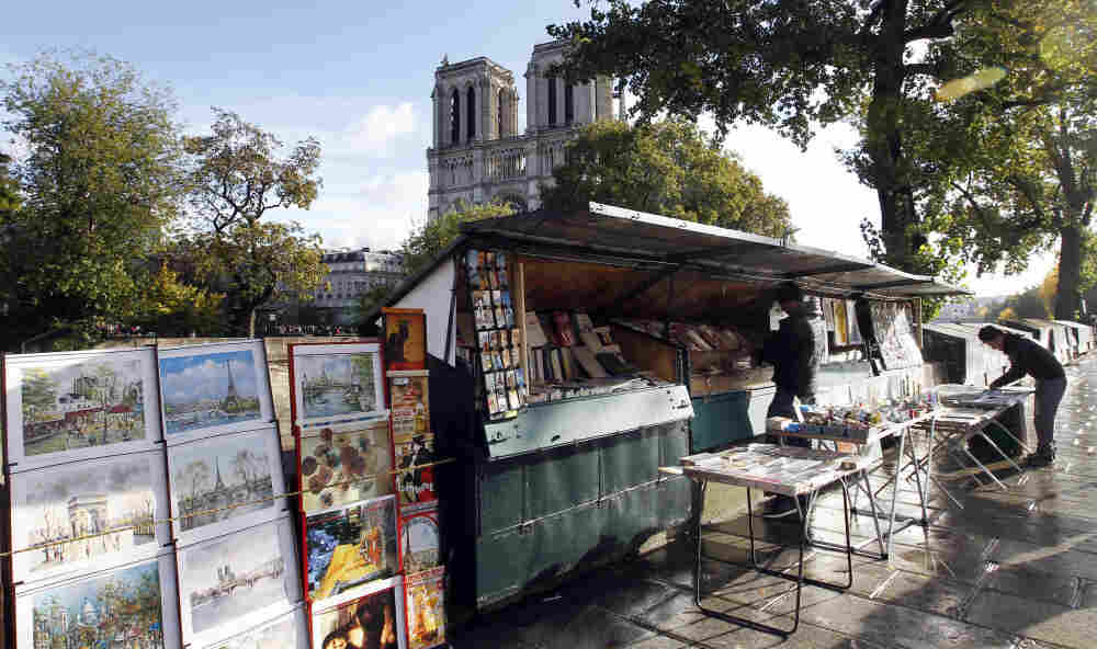 Bouquinistes set up their stalls on the promenade above the Seine river near Notre Dame Cathedral.