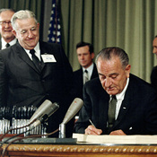 President Johnson (center) signs the Medicare Act in 1965 as Harry Truman (right) looks on.