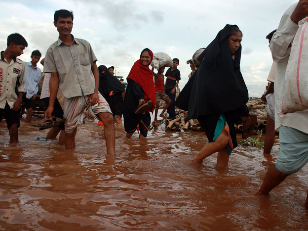 In the Cancun climate talks, officials will be discussing how rich countries can help poor countries, like Bangladesh, adapt to climate change. The low-lying nation has drawn up plans for how it would cope with rising sea levels, which are expected as a result of global warming. Here, people ford a flooded river near the port city of Chittagong.