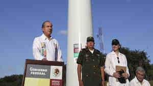 Felipe Calderon starts a wind turbine that will help power the U.N. climate talks in Cancun