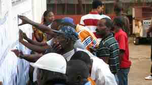 Haitians look for their names on voting lists.