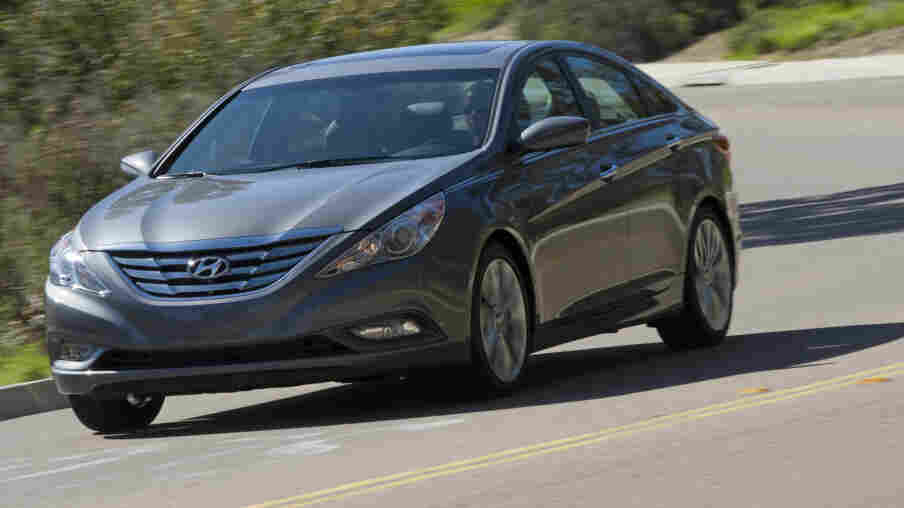 A Hyundai Sonata drives down a road.