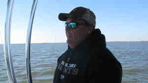 Oysterman Mitch Jurisich steers a small boat around his family's oyster beds.