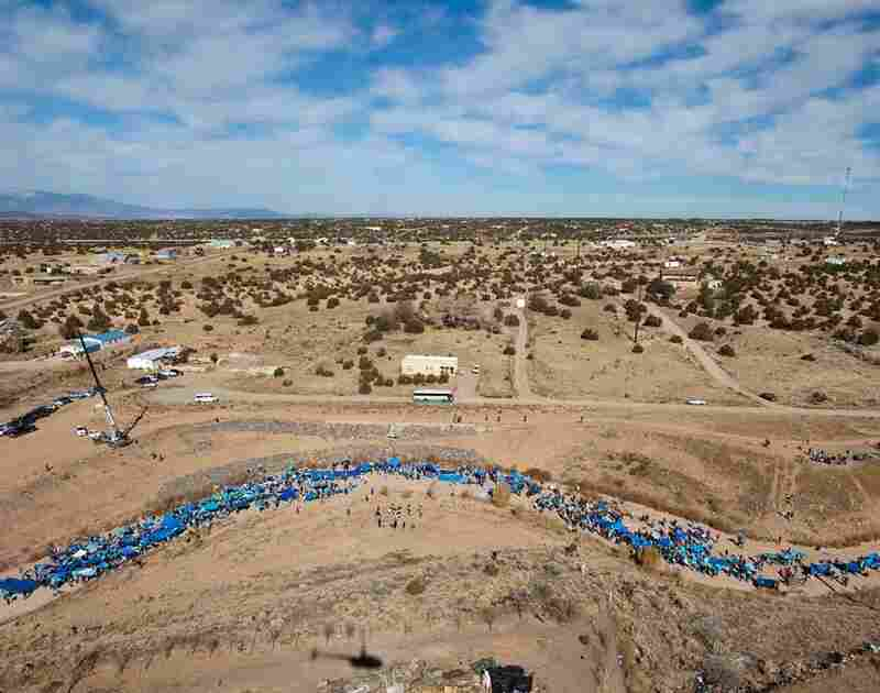 "The Santa Fe EARTH event shows how the endangered Santa Fe River could look if there were water running through it. To simulate the appearance of a river, more than 1,000 people held up blue painted pieces of cardboard or tarps.""Flash Flood"" by Santa Fe Art Institute"