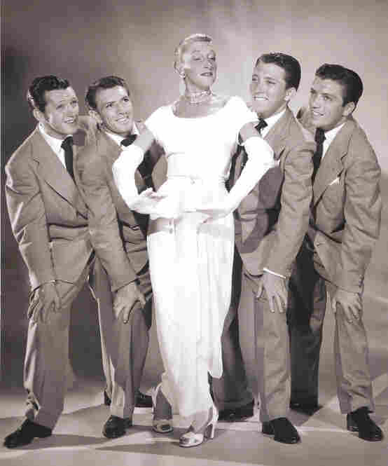 "After leaving MGM, Thompson co-created the nightclub act ""Kay Thompson and the Williams Brothers."" She poses with them here in 1947."