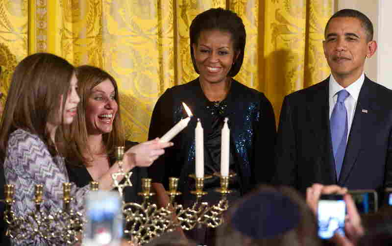 The Obamas watch as Susan Retik (second from left) and her daughter Molly light a menorah on the second night of Hanukkah during a reception in the East Room on Thursday. Cleanup crews discovered the menorah, loaned from Congregation Beth Israel in New Orleans, covered in mold, filth and sewage after Hurricane Katrina. Retik's husband, David, was killed in the Sept. 11, 2001, attacks. (Saul Loe...