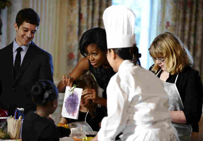 Michelle Obama displays a card made by children from a military family in the State Dining Room on Wednesday. The families were invited to make holiday ornaments, cards and treats at the White House.