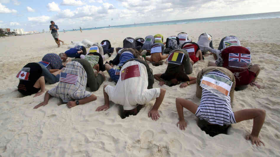 Sierra Club activists bury their heads in sand in Cancun in protest of the U.N. Climate Conference