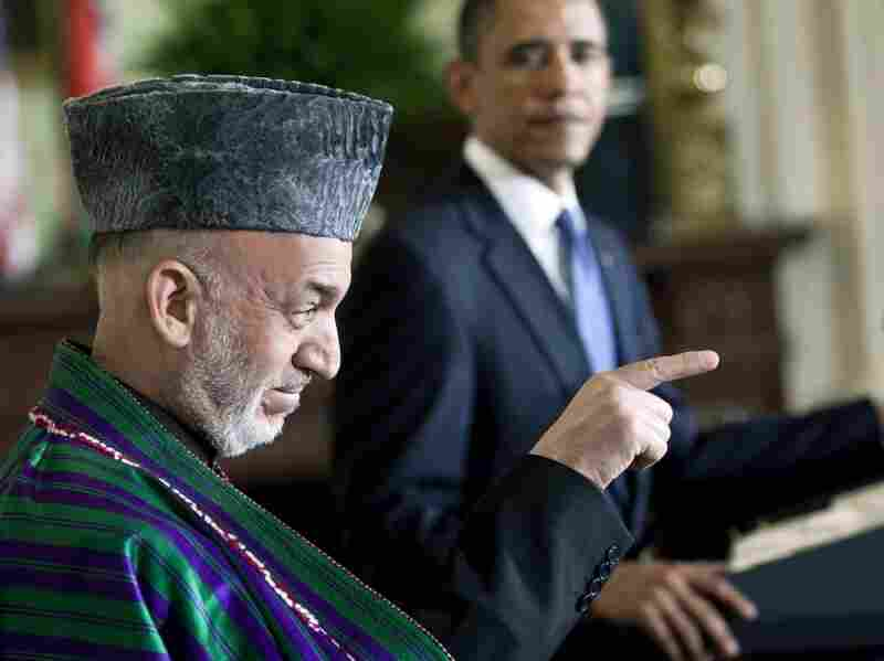 President Barack Obama watches as Afghanistan President Hamid Karzai speaks to a reporter