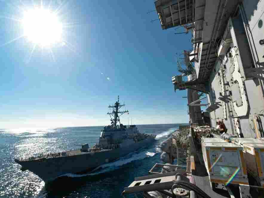 The USS John McCain (L) pulls alongside the USS George Washington in the Sea of Japan; Dec. 6.