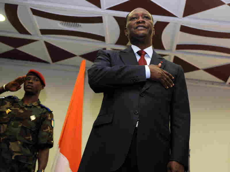Alassane Ouattara sings the national anthem during a ceremony in Abidjan