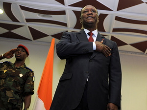 Alassane Dramane Ouattara sings the national anthem during a ceremony in a hotel in Abidjan, Dec. 4, 2010, during which he appointed a new prime minister. Opposition leader Ouattara swore himself in as Ivory Coast's new president Dec. 4, laying claim to the presidency in defiance of Gbagbo, who faces international pressure to step aside.
