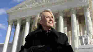 Arizona Gov. Jan Brewer stands outside the Supreme Court.