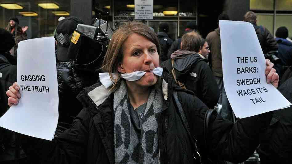 A gagged demonstrator holds placards