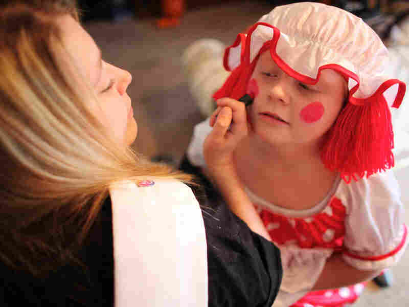 Michelle Fridley helps her daughter, Felicia, get dressed up to go to a Halloween party.