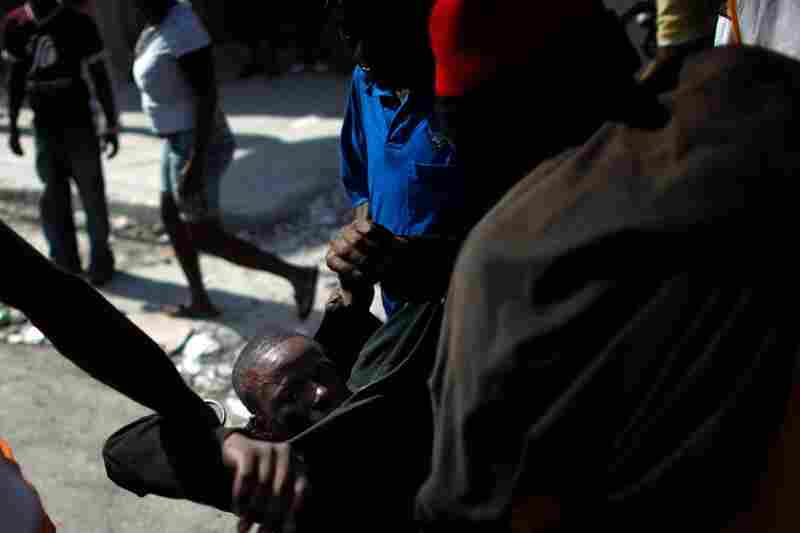 U.N. peacekeepers and the joint Organization of American States-Caribbean Community observer mission say the election problems do not invalidate the vote. Here, protesters help an injured man who was hit in the head with a rock.
