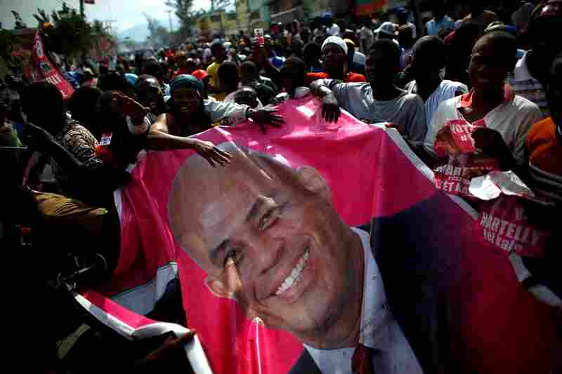 Supporters carry a giant poster of Martelly in a massive demonstration. Officials acknowledged that the election was imperfect, with hundreds of thousands of earthquake dead still registered and many living voters waiting for ID cards.