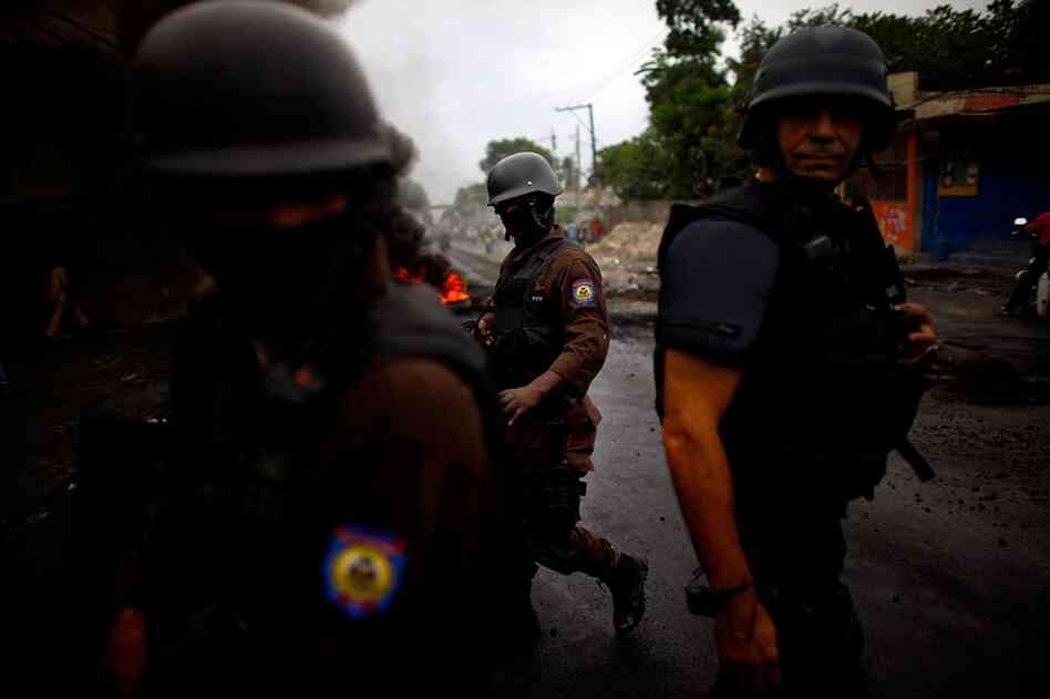 """U.N. police make their way through the streets on Thursday in Petionville, a suburb of Port-au Prince. Supporters of Michel Martelly, Sweet Mickey"""" took to the streets of Haiti's capital for a third day to contest election results. Haitian election offi"""