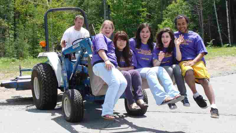 Local and international students ride on a tractor through school campus.