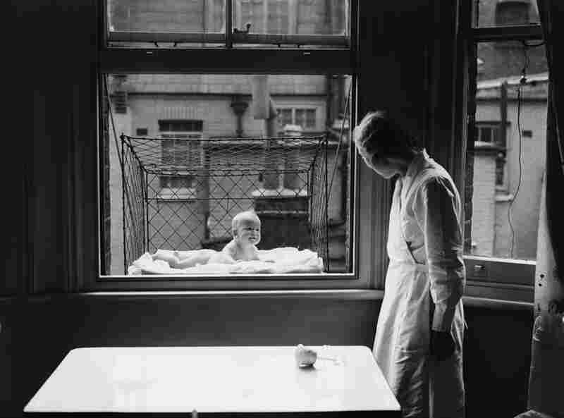 """Afraid your baby's not getting enough fresh air? Simply place it in a wiry basket precariously dangled from your high-rise apartment window. A nanny """"supervises"""" a baby in a tenement building, 1937."""