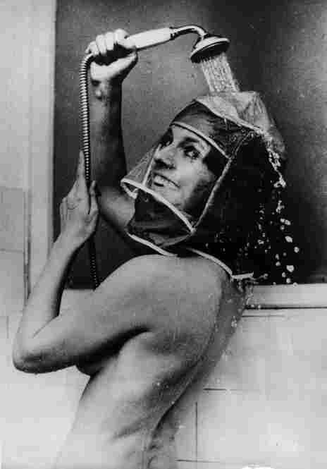 """To prevent her makeup from running and her hair from getting wet, an actress demonstrates the """"new"""" shower hood, which probably had the effect of steaming her makeup right off."""