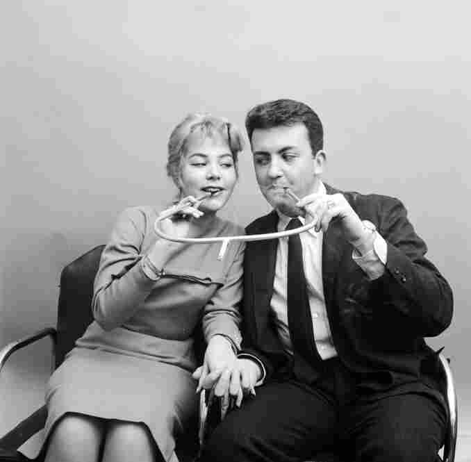 Daisy, Daisy, give me your answer, do. Would you like to smoke a cigarette in this romantic holder built for two?Image circa 1955