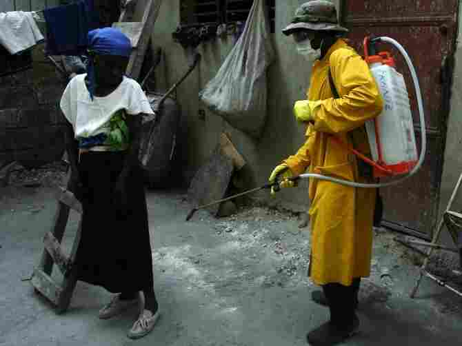 Health workers at a tent city on the outskirts of Haitian capital Port-au-Prince disinfect a house