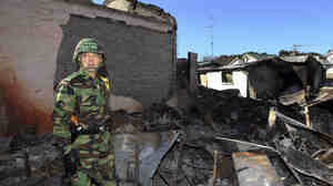 South Korean Gen. Han Min-koo looks at houses destroyed by North Korean shelling on Yeonpyeong Island.