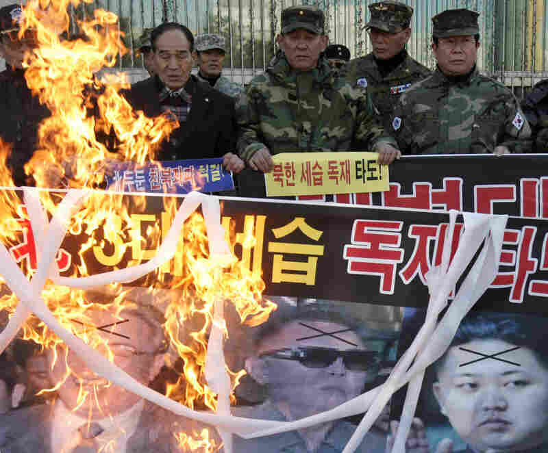 South Korean veterans burn a banner showing photos of North Korean leaders.