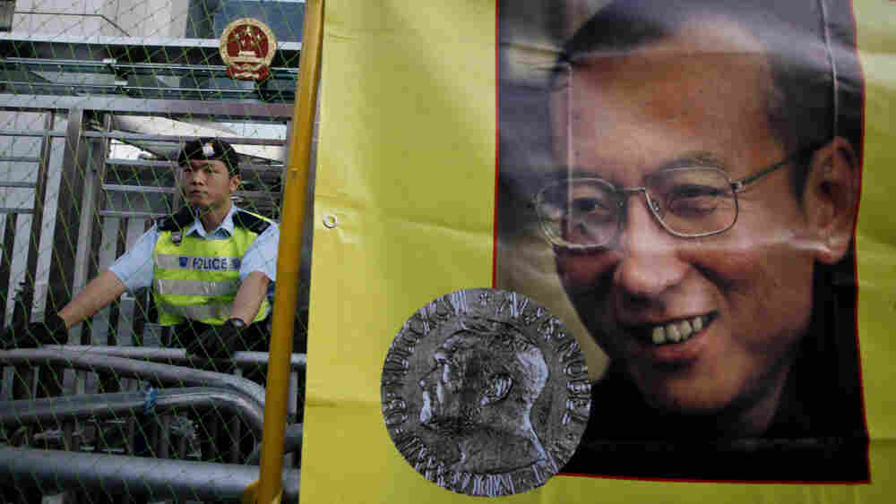 A police officer stands guard besides a picture of jailed Chinese dissident Liu Xiaobo.
