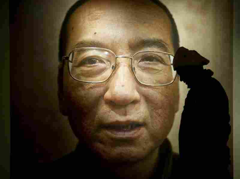 A man in Oslo walks in front of a poster of Liu Xiaobo.