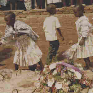 An undated image shows three children and a woman laying wreaths on a mass grave