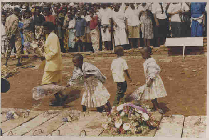 An undated image shows three children and a woman laying wreaths on a mass grave of genocide victims