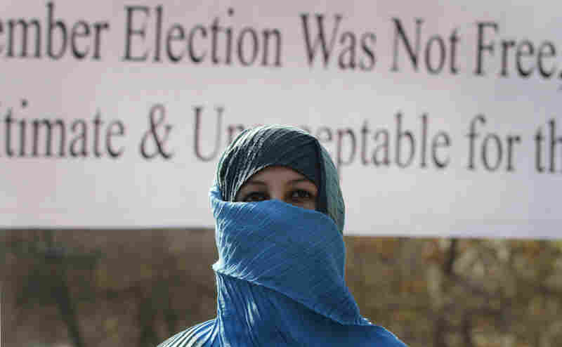 A former Afghan legislator covers her face during a march against voting irregularities