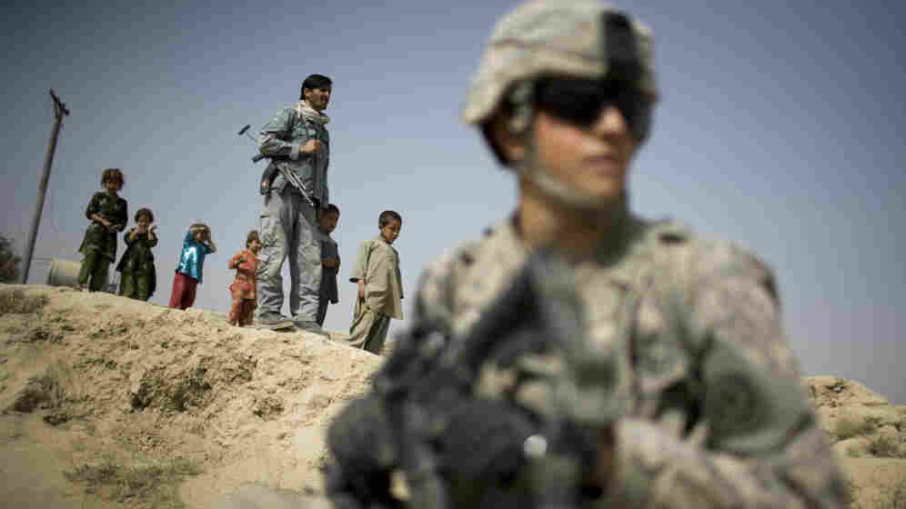 Children and an Afghan policeman look at a U.S. soldier on patrol in Kandahar