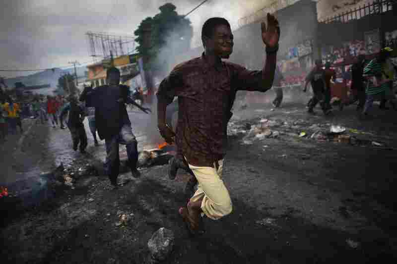 Supporters of Michel Martelly run from tear gas fired by U.N. soldiers.