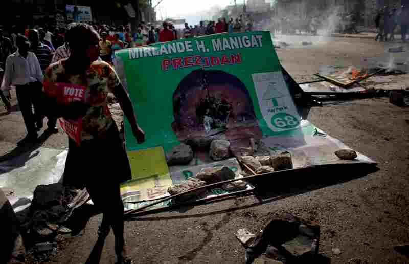 Martelly supporters take to the streets, walking past a smashed billboard of Manigat.