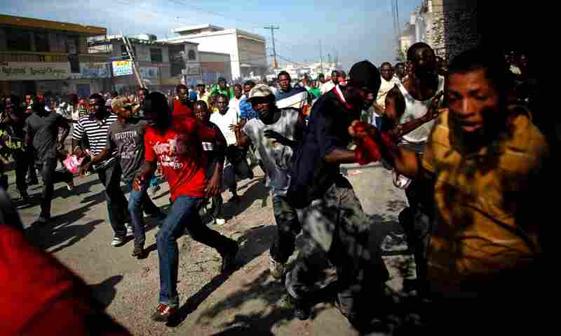 Martelly supporters run from tear gas fired from an election office in Port-au Prince on Wednesday. On Tuesday night, demonstrators set up flaming barricades near a restaurant in Petionville, a suburb of the capital where the tallies were announced, and threw rocks at passersby.