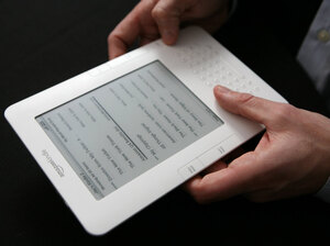 A Kindle e-reader in someone's hands.