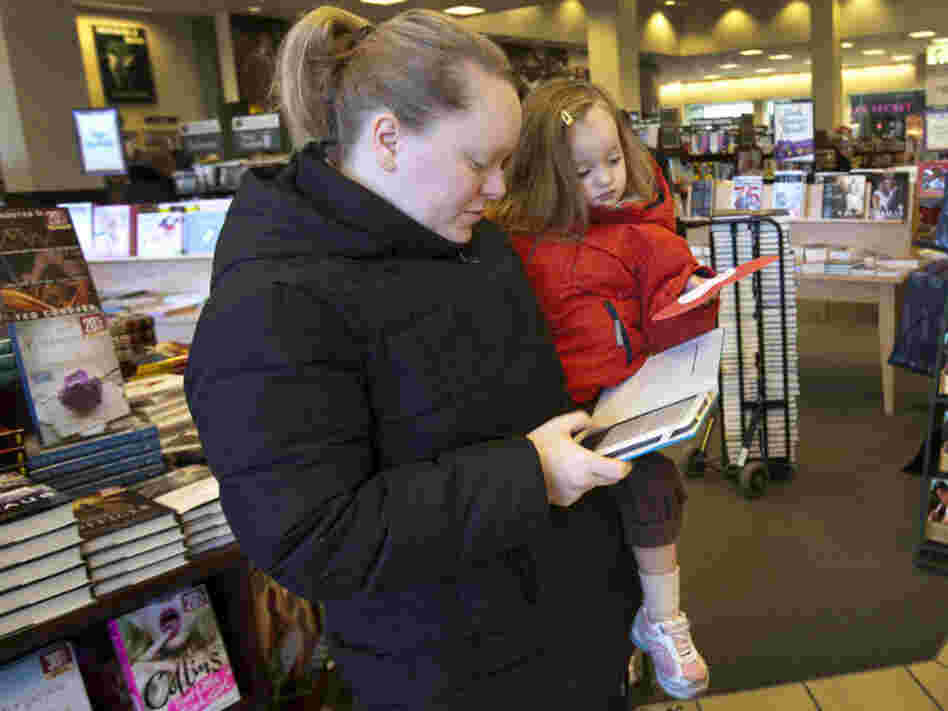 Emily Fernandez, holding her daughter Bethany, uses her Nook e-reader to browse some books.