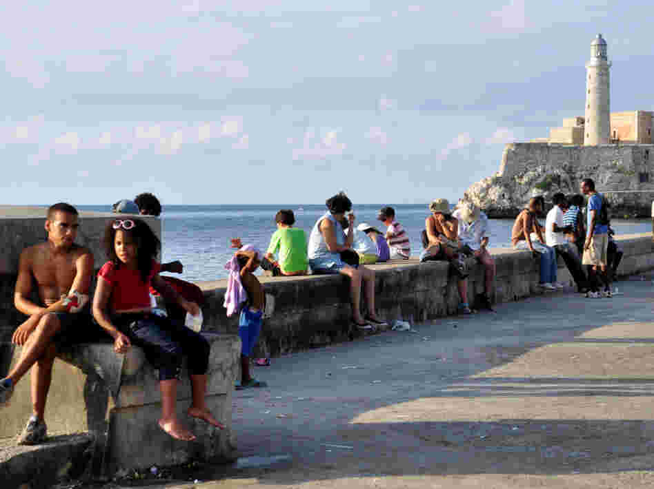 Tourists and locals sit on a wall along the waterfront in Havana; Aug. 25, 2010.
