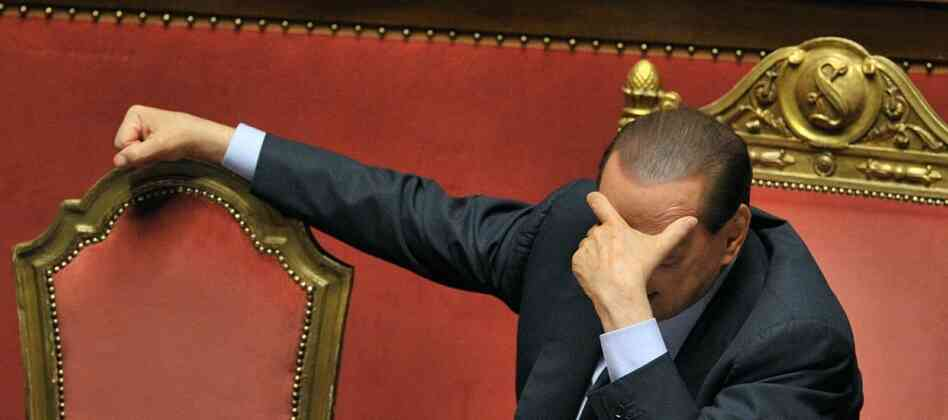 Italian Prime Minister Silvio Berlusconi reacts after delivering an address to the Italian Senate on