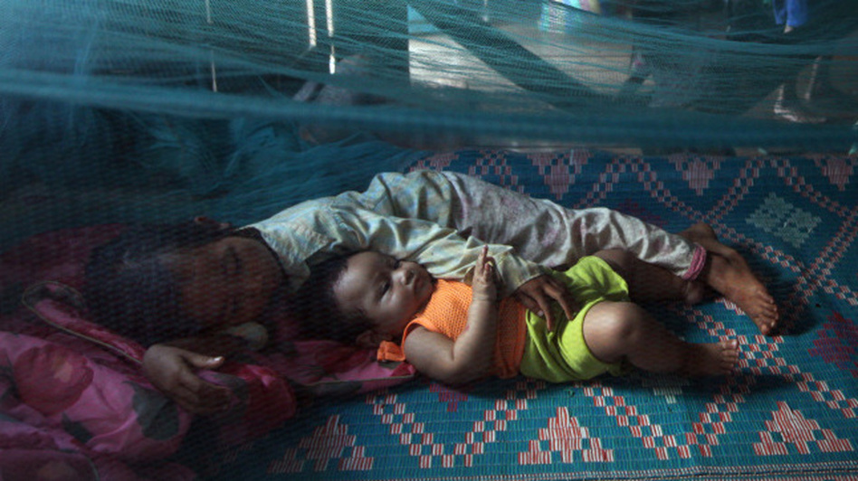 Two sisters rest under a mosquito net during a July monsoon rain in Prey Mong kol village in Cambodia's Pailin province. (Getty Images AsiaPac)