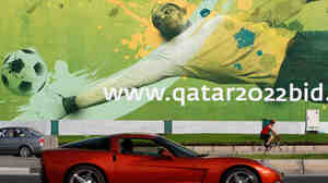 A car drives past a World Cup ad in Qatar.