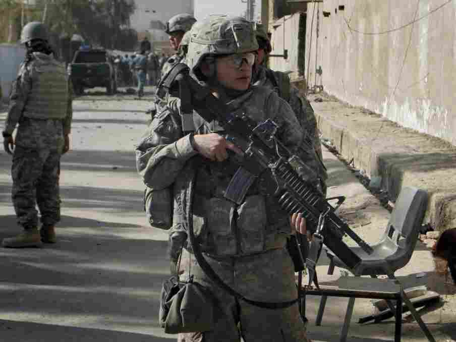 """A U.S. soldier stands guard near the scene of an explosion in Kandahar, Afghanistan, on Dec. 11, 2010. The U.S. strategic review on the war in Afghanistan says progress is being made in the country, but it is """"fragile."""""""
