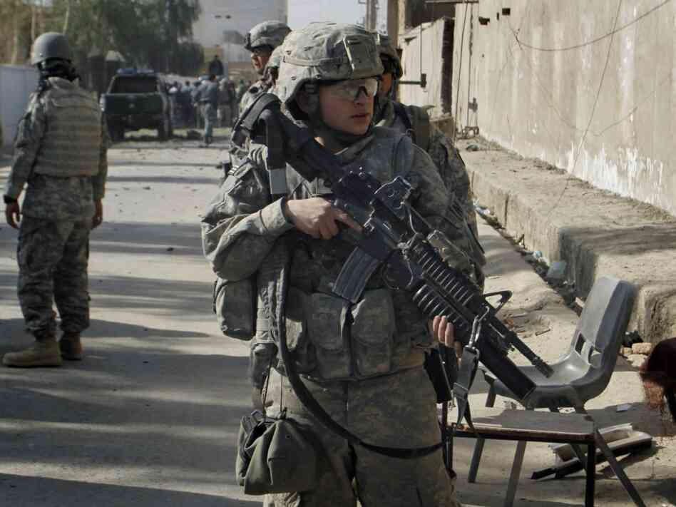 "A U.S. soldier stands guard near the scene of an explosion in Kandahar, Afghanistan, on Dec. 11, 2010. The U.S. strategic review on the war in Afghanistan says progress is being made in the country, but it is ""fragile."""