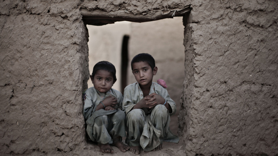 Afghan brothers Barangai (R), 6, and Shaista Khan, 4, pose for a portrait just outside a U.S. Marines combat outpost in Marjah, Helmand province, southern Afghanistan, on April 11, 2010.